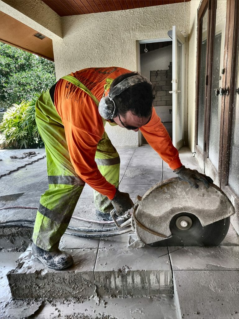 Concrete cutter with a raincoat cutting a slab.